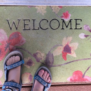 "Image of two feet, one prosthetic and one meaty, wearing blue-green tevas and standing on a faded green mat that reads ""Welcome"" and has printed flowers."