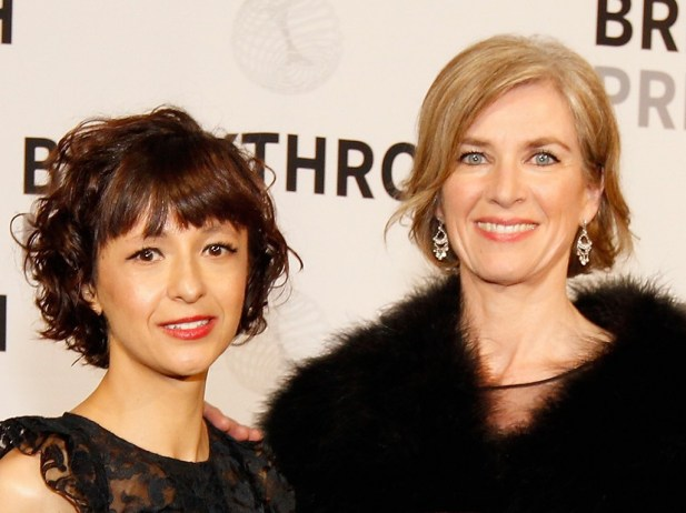 Bust shot of Emmanuelle Charpentier (left; shorter woman with brown hair in a bob, wearing earrings and a black top) and Jennifer Doudna (right; taller, white woman with blond hair tied back, wearing earrings and a fuzzy black top) standing in front of a yellow backdrop and smiling at the camera