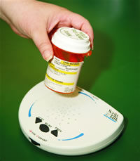 bar code labeler reading the bar code on a bottle of medication held by a white hand