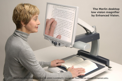 The Merlin desktop magnifier being used to magnify book text. A white woman in her mid 60's is reading the text from the book off of the magnifier's screen.