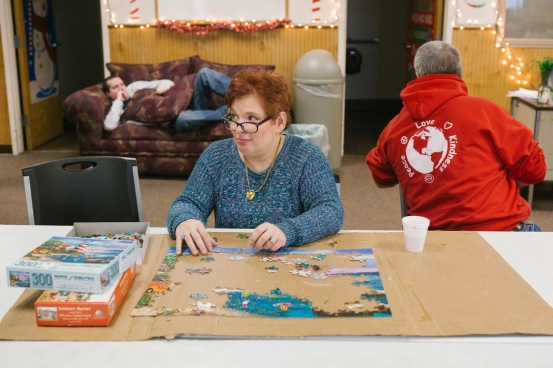 Pauline sitting at a table working on a jigsaw puzzle