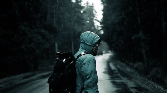 Hooded backpacker walking on a dark road in the rain looking back at the camera ominously